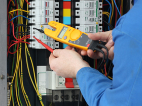 electrician testing for voltage at a fuse box