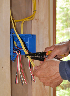electrician hand stripping insulation off of a wire
